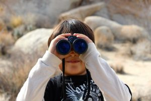 Photograph of a kid with binoculars