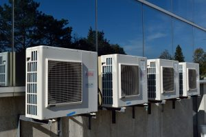 A photograph of some air conditioner units stationary outside of a building
